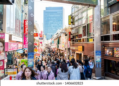 Tokyo, Japan - April 2, 2019: Famous Takeshita street in Harajuku with crowd of many people walking by restaurant buildings