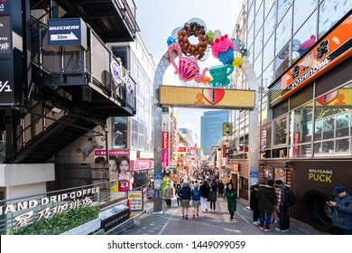 Tokyo, Japan - April 2, 2019: Famous Takeshita street in Harajuku with crowd of people walking by restaurant shops stores buildings by entrance arch sign