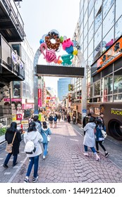 Tokyo, Japan - April 2, 2019: Famous Takeshita street road in Harajuku with crowd of people walking by restaurant shops stores buildings by entrance arch sign