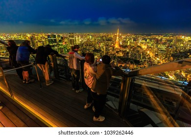 Tokyo, Japan - April 20, 2017: people takes a picture of Tokyo Skyline and Tokyo Tower from atop of Mori Tower in Roppongi Hills complex, Minato District, Tokyo, Japan.