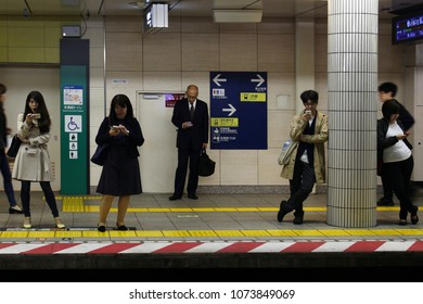 TOKYO, JAPAN - April 20, 2018: Passengers on a platform at Ebisu subway station use their mobile phones as they wait for a Hibiya Line train to arrive.
