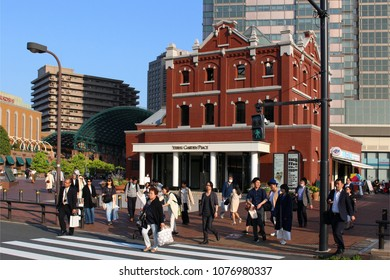 TOKYO, JAPAN - April 20, 2018: People crossing the street in front of the Ebisu Garden Place development.