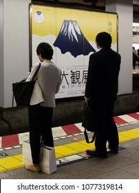 TOKYO, JAPAN - April 20, 2018: Passengers wait on a platform at Ebisu subway station. A poster with a picture of Mount Fuji on it advertsing a Yokoyama Taikan exhibition is between the platforms.