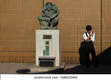 TOKYO, JAPAN - April 20, 2018: A bronze statue of Ebisu, a good luck symbol, in front of Ebisu Station.