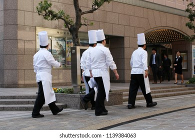 TOKYO, JAPAN - April 20, 2018: A group of toque-clad chefs walking past the Takarazuka Theater in Hibiya central Tokyo.