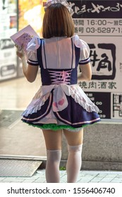 Tokyo / Japan - April 20, 2018: Young girl dressed in flirtatious french maid costume calling on passerby to visit the Maid Cafe in Akihabara district of Tokyo, Japan