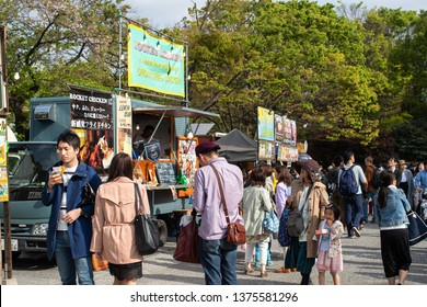 Tokyo, Japan - April 20, 2019: Earth Day in Yoyogi park in Tokyo. People go and eat near food truck with fried chicken