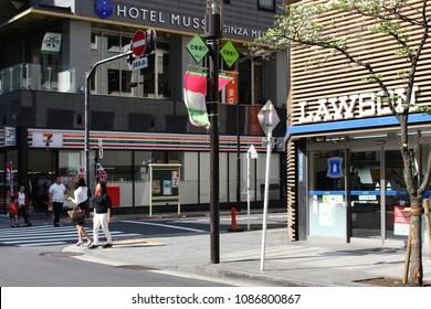 TOKYO, JAPAN - April 21, 2018: A street corner in Ginza, central Tokyo, with a 7-Eleven convenience store on one side of the street and a rival Lawson convenience store on the other.