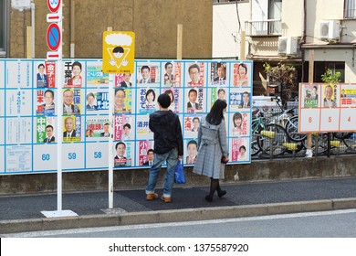 TOKYO, JAPAN - April 21, 2019: People look at a noticeboard in Tokyo's Koto Ward with posters of candidates standing in local elections for the local assembly.