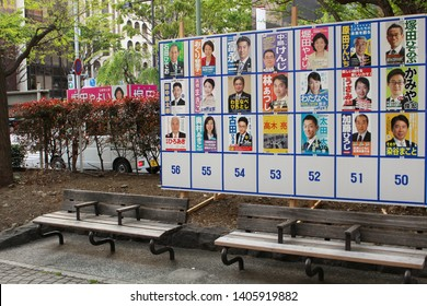 TOKYO, JAPAN - April 21, 2019: A noticeboard in a park in Tokyo's Chuo Ward with posters of candidates standing in local assembly elections. A candidate's election campaign van is in the background.