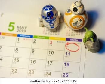 TOKYO, JAPAN - APRIL 22, 2019 - Star Wars Figures (Yoda, BB8 & R2-D2) on a calendar sheet looking at May the 4th
