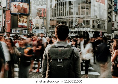 TOKYO, JAPAN - APRIL 23, 2018:  the man stand in view of Shibuya Crossing, one of the busiest crosswalks in the world.  Long Exposure