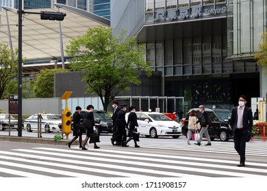 TOKYO, JAPAN - April 23, 2020: People, including a group of JR train staff,  using a crosswalk in Yaesu by Tokyo Station. They wear face masks & the street is quiet due to coronavirus outbreak.