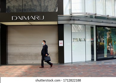 TOKYO, JAPAN - April 23, 2020: A man wearing a protective face mask walks past Daimaru department store in Yaesu by Tokyo Station. It is temporarily closed & shuttered due to coronavirus outbreak.