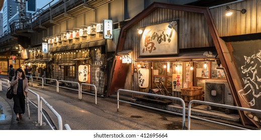 TOKYO, JAPAN - APRIL 28TH, 2016: Small Japanese restaurants at the Yurakucho Alley under elevated Japan Railway rail tracks..