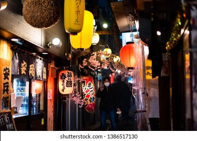 Tokyo, Japan - April 3, 2019: Memory lane alley with decorations and yellow paper lamps lanterns and people in Shinjuku area of city at night