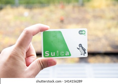 Tokyo, Japan - April 30, 2019 : Man hold Suica pass with the blurred background, Suica is a prepaid card for travelling with train, bus and shopping in Japan.