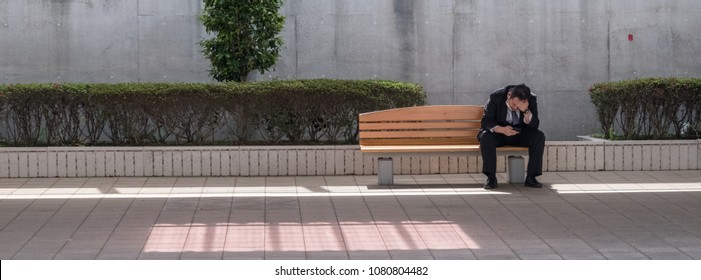TOKYO, JAPAN - APRIL 30TH, 2018. Commuters sitting on a bench at Japan Railway Station platform waiting for the train