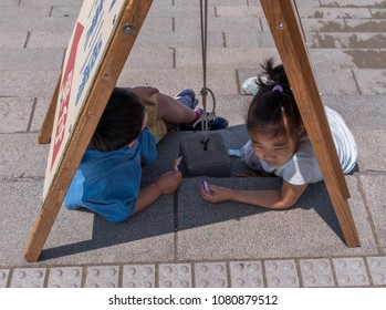 TOKYO, JAPAN - APRIL 30TH, 2018. Young children finding cover in the shade under a signboard during a hot day in Enoshima Island