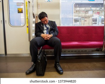 TOKYO, JAPAN - APRIL 4, 2019: A tired salaryman falls asleep on a JR railway train during a long commute after work home. Travel and lifestyle.