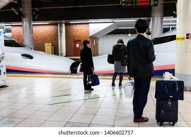 Tokyo, Japan - April 5, 2019: Train station platform in Ueno with shinkansen and salaryman people with baggage waiting by car