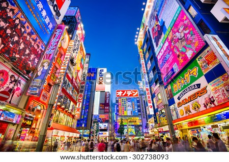 TOKYO, JAPAN - AUGUST 1, 2015: Crowds pass below colorful signs in Akihabara. The historic electronics district has evolved into a shopping area for video games, anime, manga, and computer goods.