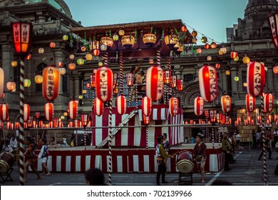 TOKYO, JAPAN - AUGUST 10 2012: Paper lanterns and the stage of the Tsukiji Honganji Bon Odori Matsuri - the popular festival in Tokyo. Text on the lanterns are names of the festival sponsors.