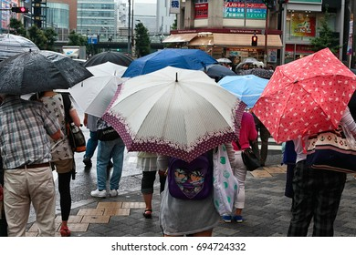 TOKYO, JAPAN - AUGUST 10, 2016: People shop in rain on August 10, 2016 in Shinjuku district, Tokyo. Shinjuku is districts of Tokyo, with many international corporate located.