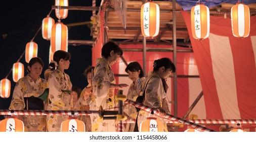 TOKYO, JAPAN - AUGUST 12TH, 2018. Dancers in traditional yukata dancing on the stage at the Bon Odori celebration in Shimokitazawa neighborhood at night.