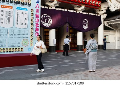 TOKYO, JAPAN - August 15, 2018:  Front of Ginza 's Kabuki-za kabuki theater where a worker uses a loudspeaker to give details of the evening performance. The billboard has information on kabuki casts.