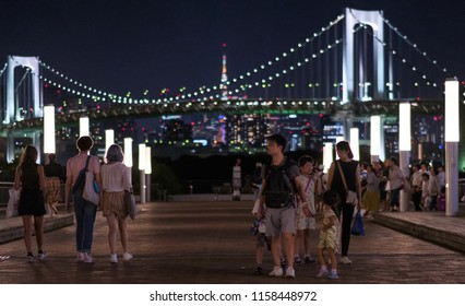 TOKYO, JAPAN - AUGUST 15TH, 2018. People walking at Odaiba walking path at night with Tokyo Rainbow Bridge in the background