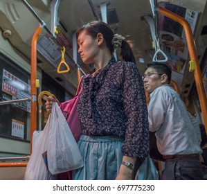 TOKYO, JAPAN - AUGUST 16TH, 2017. Commuters in a public bus in Tokyo.