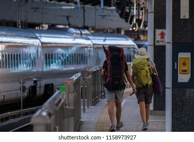 TOKYO, JAPAN - AUGUST 17TH, 2018 .  Backpackers tourist couple at Tokyo Railway Station platform.
