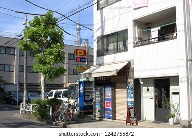 TOKYO, JAPAN - August 18, 2018: View of street in Toyko's Sumida Ward with vending machines, car park and Tokyo Skytree towering over buildings in the background.