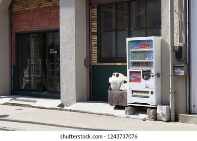 TOKYO, JAPAN - August 18, 2018: A drinks vending machine with attached wooden trash can holder in front of a building company's office with a model of Tower Tower in its window in Toyko's Sumida Ward.