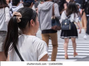 TOKYO, JAPAN - AUGUST 19TH, 2018. Japanese girl waiting to cross  the street in Shibuya.