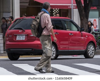 TOKYO, JAPAN - AUGUST 19TH, 2018.  Old man crossing the street at the famous Shibuya scramble.