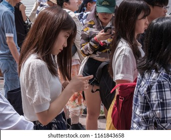 TOKYO, JAPAN - AUGUST 19TH, 2018. Pretty Japanese girl with smartphone waiting to cross the street in Shibuya.
