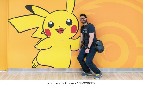 Tokyo, Japan - August 2018: Happy tourist with a Pokemon Pikachu figure at Pokemon Center store in Sunshine City shopping mall
