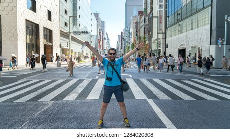 Tokyo, Japan - August 2018: Happy and excited tourist at hopping district Ginza with famous Chuo Dori street that closes to cars on Sundays and becomes a pedestrian street