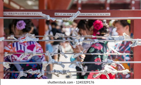 Tokyo, Japan - August 2018: Japanese girl who select a bad fortune from Japanese fortune telling strip, Omikuji, tying his bad fortune paper with a pole to leave it at Sensoji temple, Asakusa.