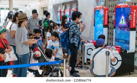 Tokyo, Japan - August 2018: Parents with their children playing Pokemon branded arcade video games at Pokemon Center