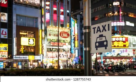 Tokyo, Japan - August 2018: Taxi sign under bright neon and advertisement lights at Kabukicho in the Shinjuku, Tokyo, Japan