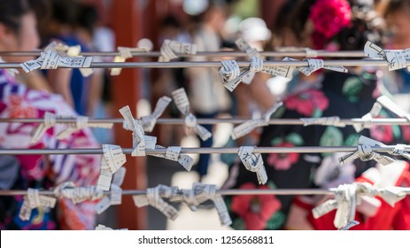 Tokyo, Japan - August 2018: Unidentified people who select a bad fortune from Japanese fortune telling strip, Omikuji at Sensoji temple, Asakusa.