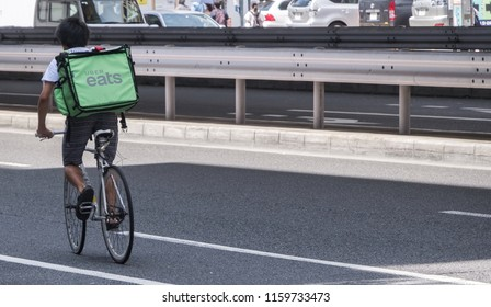 TOKYO, JAPAN - AUGUST 20TH, 2018. Uber Eats rider cycling in the street of Roppongi.