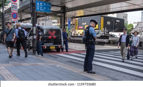 TOKYO, JAPAN - AUGUST 20TH, 2018. Policeman writing a summon at Roppongi street sidewalk.
