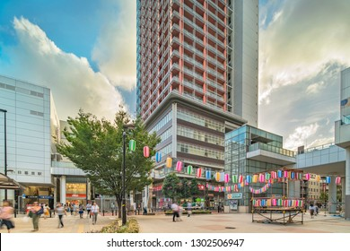 TOKYO, JAPAN - August 23 2018: View of the square in front of the Nippori train station decorated for the Obon festival in the sunset summer sky with a yagura tower and paper lanterns in Tokyo.