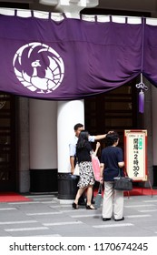 TOKYO, JAPAN - August 24, 2018: View of the front of Ginza 's Kabuki-za kabuki theater where a worker is helping visitors in front of a curtain with the theater's phoenix motif.