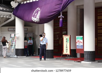 TOKYO, JAPAN - August 24, 2018: At the front of Ginza 's Kabuki-za, a kabuki theater, a worker uses a loudspeaker to announce details of the matinee performance.
