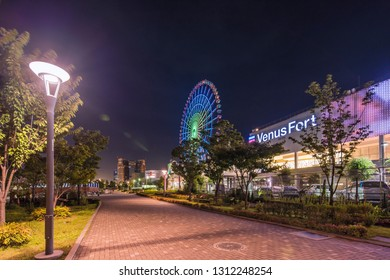 TOKYO, JAPAN - August 24 2018: Odaiba illuminated Palette Town Ferris wheel close to the Venus Fort commercial area in the summer night sky. Passengers can see the Tokyo Tower, the twin-deck Rainbow B